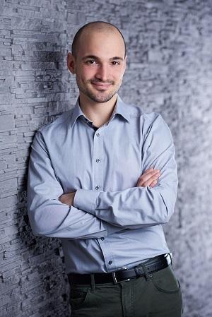 Auf dem Bild ist Michael Simon in einem Hemd zu sehen, wie er sich gegen eine Wand lehnt.